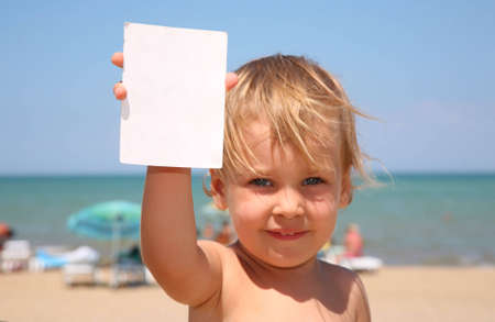 The child holds a paper. photo