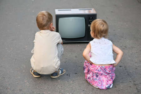children on the road in the old television set Stock Photo