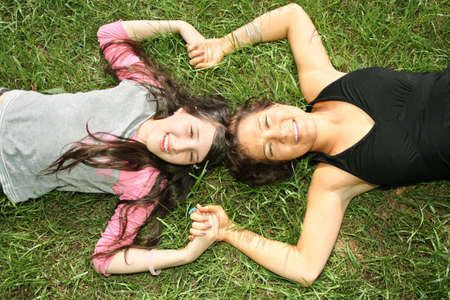 mother and daughter lie on the grass photo