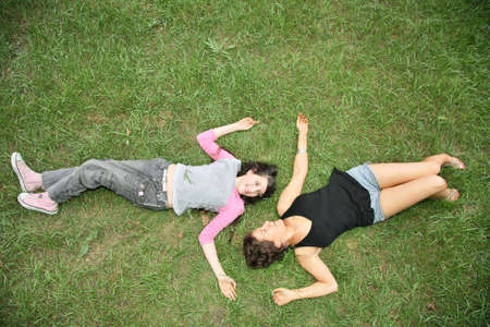 mother and daughter-teenager lie on the grass photo