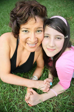 woman and teenager lie on the grass photo