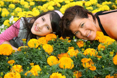 Mother and daughter lie among flowers photo