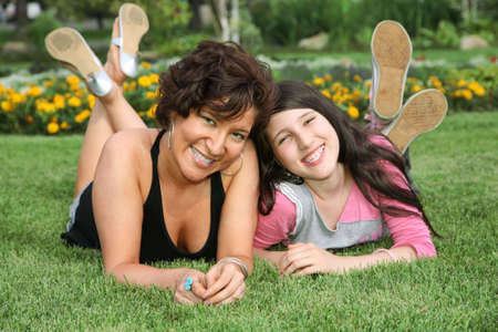 mother and daughter lie on the grass and smile photo