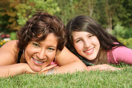 mother and daughter lie on the grass and smile 2 photo