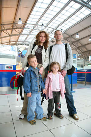 airport people: standing traveling family of four