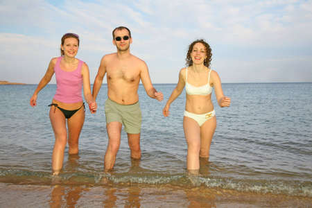 Man and two girls leave the sea photo