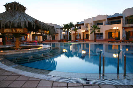 Evening shot of swimming pool in tropical hotel photo