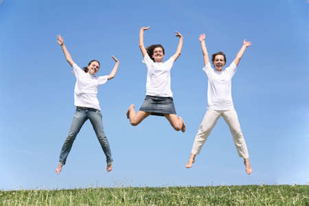 waved: Three girlfriends in white T-shorts jump having waved hands