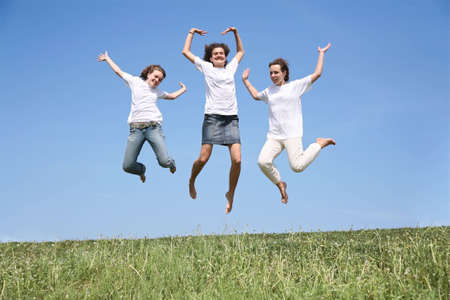 simultaneously: Three girlfriends in white T-shorts jump simultaneously