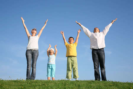 family praying: family of four on grass with hands up