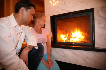 burning man: man, woman and fireplace Stock Photo