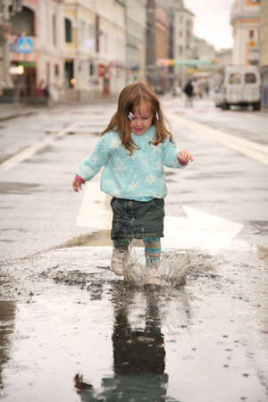 girl on street in puddle photo