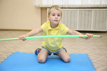 exersice: boy makes the exersice with rod 2
