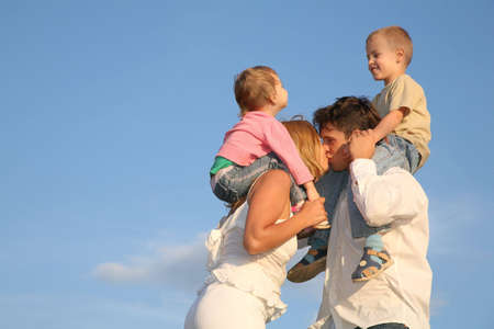 kissing parents with children on shoulders photo