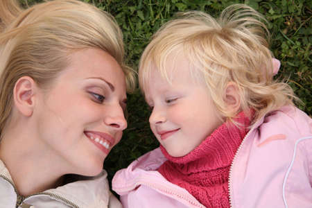 mother and daughter lie on the grass and look at each other photo