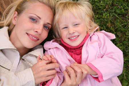 mother and daughter lie on the grass and look upward  2 photo