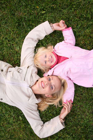 mother and daughter lie on the grass and look upward 3 photo