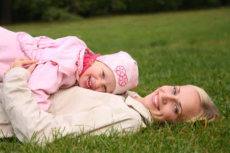 untruth: mother lies on the grass, daughter lies on it Stock Photo