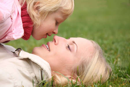 and lies: mother lies on the grass, daughter lies on it 2