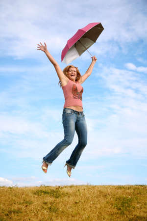 young woman jumps with the umbrella on to the meadow photo