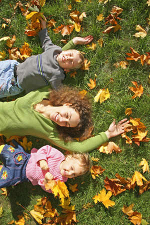 woman with the son and the daughter they lie on the grass photo