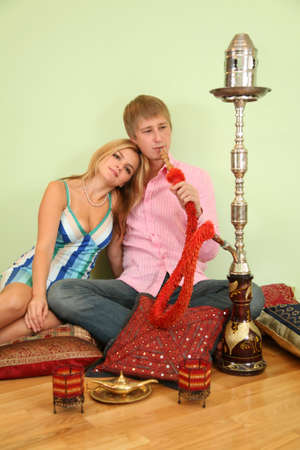 couple sit on pillow and smoke hookah photo