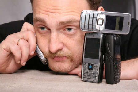 speaks: man with beard speaks on the cell phone, relying on the table Stock Photo