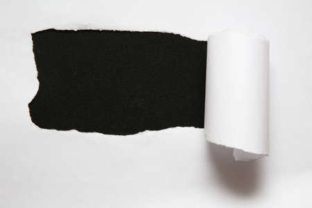 the sheet of torn paper against the black background photo