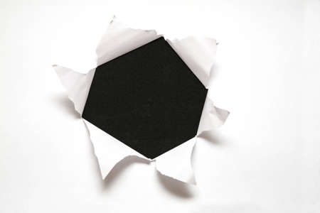 the sheet of paper with the hole against the black background Stock Photo - 2314019