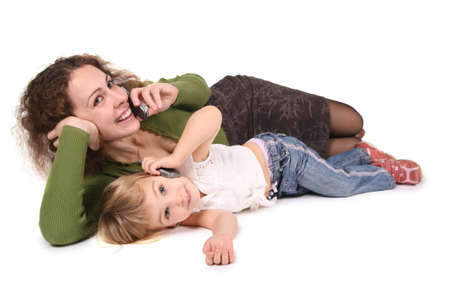 mother and daughter lie they talk on the cell phones on the the white