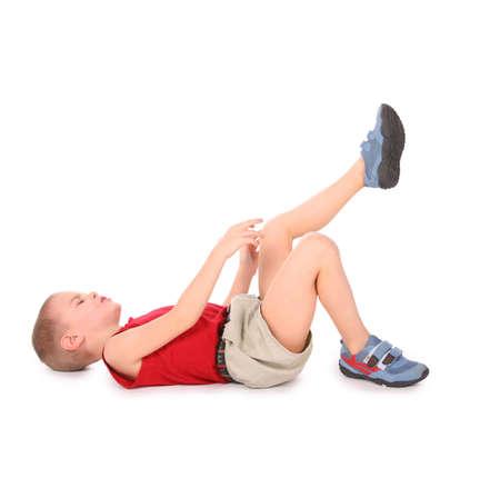 leg pain: boy lie isolated on white. pain leg Stock Photo
