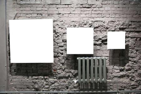 gallerie: three blank frames on grey brick wall