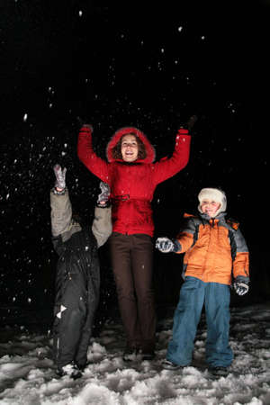 children and mother throw snow in the night 3 photo