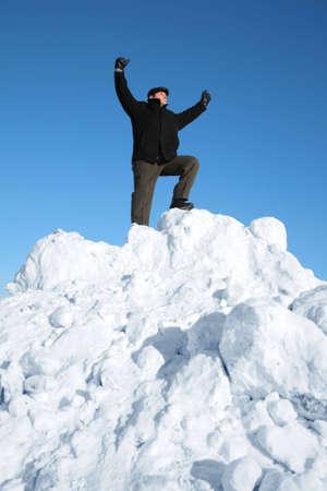 in a pile: anciano en la cima de la colina de nieve con la mano hasta