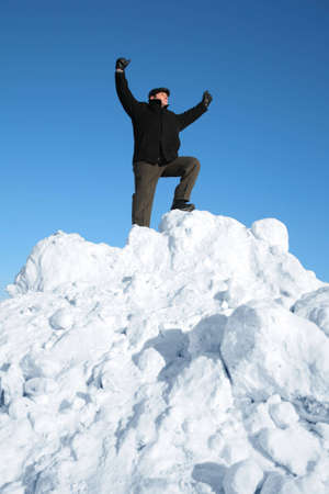 heap up: elderly man on top of snow hill with hand up