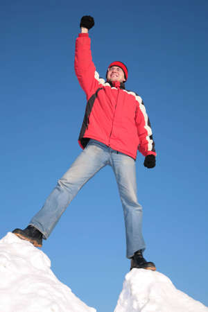 man in red jacket on top of snow hill with hand up Stock Photo - 3016154
