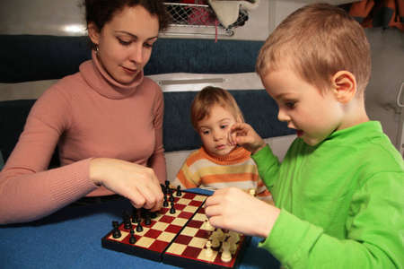 compartment: mother and son play chess in train`s compartment Stock Photo