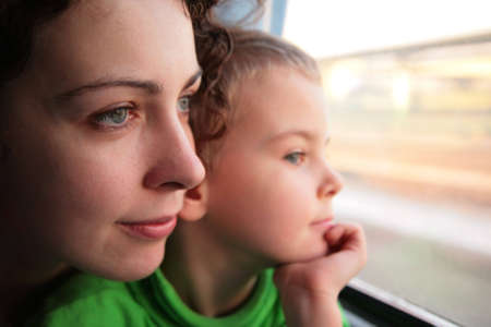 mother and son look in train`s window photo