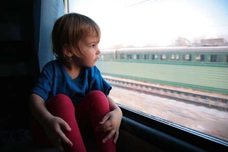 little girl  looks in train`s window photo