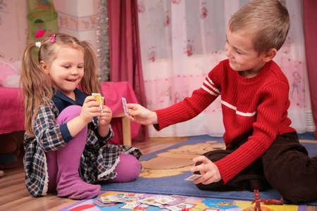 playroom: dos hijos jugar a las cartas en juego