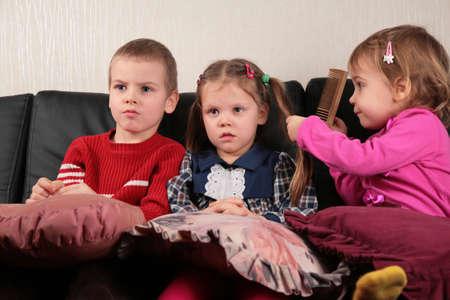 three children on sofa watching tv