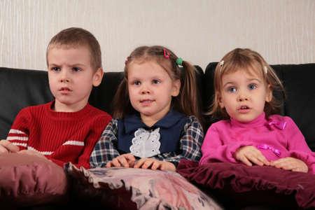 three children on sofa 2 watching tv photo