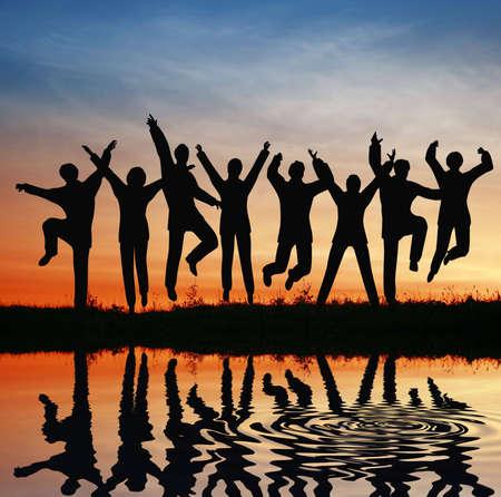 jovenes empresarios: silueta salto equipo. puesta de sol estanque