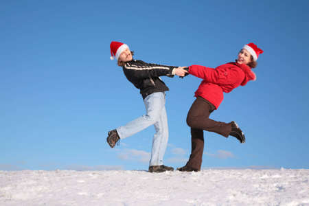 couple dance on  snow hill in santa claus hats 2 photo