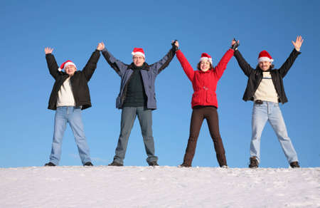 four friends greetings on snow  in santa claus hats photo
