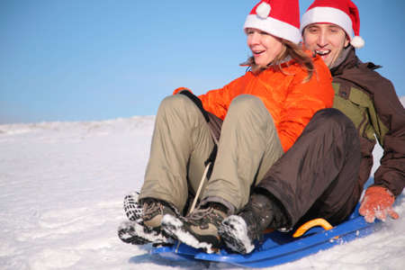man and woman in santa claus hats ride on sled Stock Photo - 3023441