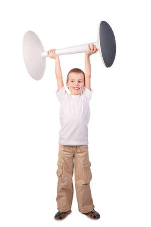 heaviness: Boy lifts stool Stock Photo