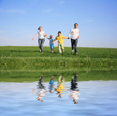 family of four running grass sky water Stock Photo - 3025272