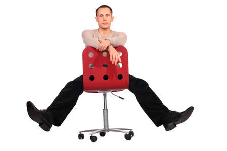 spread legs: Young man sits on red chair spread legs
