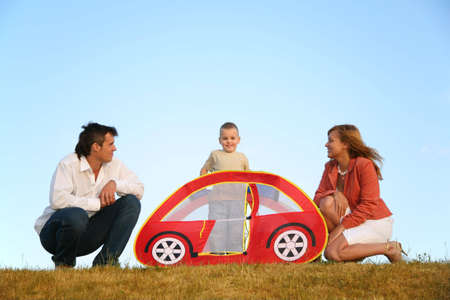 family and the toy tent on meadow photo